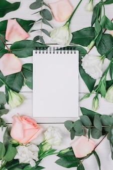 Bloco de notas espiral em branco, rodeado de rosa e flores na mesa de madeira