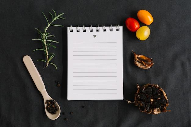 Bloco de notas espiral rodeado com alecrim; tomate cereja; pimenta preta e alho