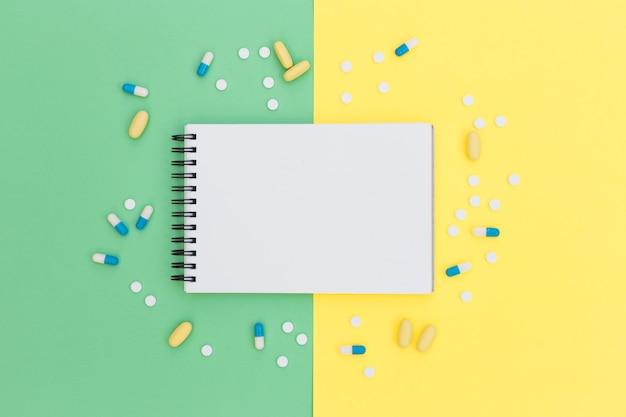 Bloco de notas espiral rodeado com pílulas em fundo verde e amarelo