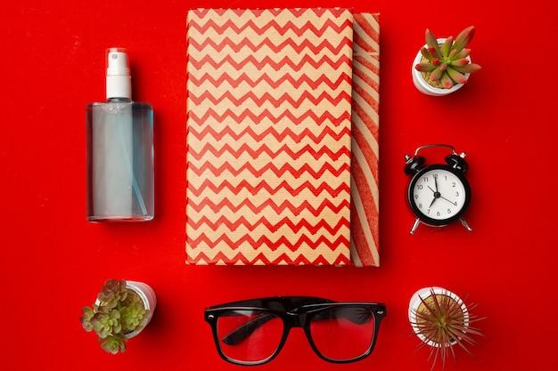 Bloco de notas fechado com copos, vasos de flores e desinfetante para as mãos em fundo vermelho