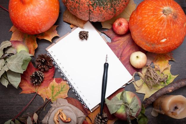 Bloco de notas, folhas de outono, frutas e vegetais na mesa de madeira