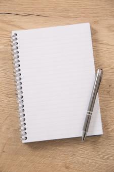 Bloco de notas forrado de branco com uma encadernação de arame de metal e uma caneta de prata aberta sobre uma superfície de madeira.