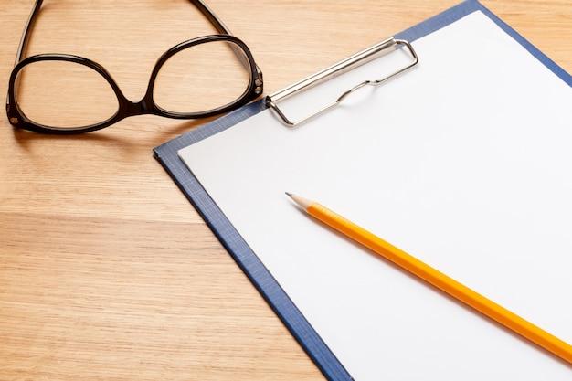 Bloco de notas, lápis e óculos no fundo de madeira