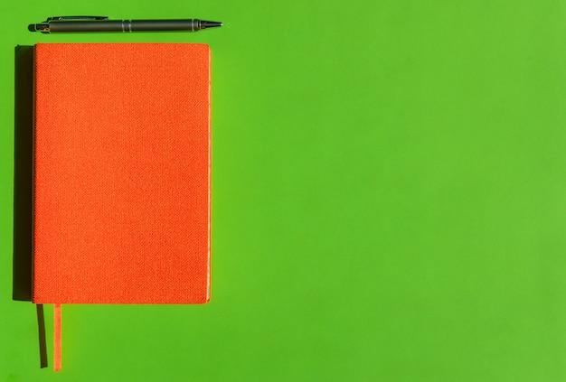 Bloco de notas laranja brilhante e caneta cinza elegante sobre fundo verde