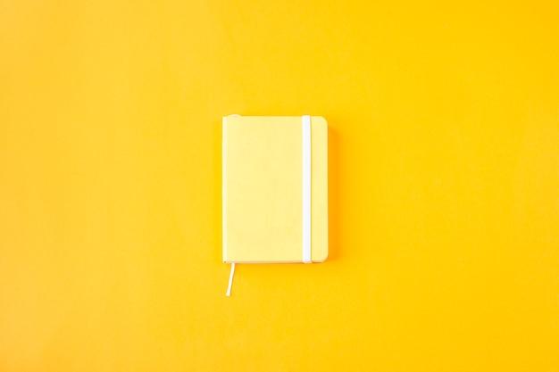 Bloco de notas minimalista amarelo para entradas em um fundo amarelo