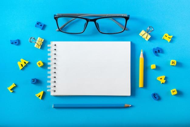 Bloco de notas mocap. óculos e letras de madeira sobre um fundo azul. conceito do dia do professor e de volta à escola.
