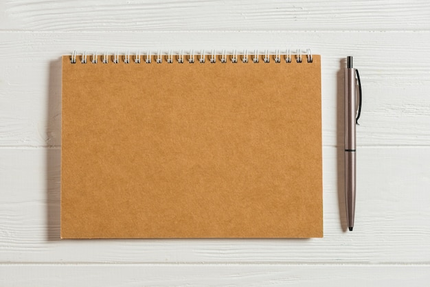 Bloco de notas na mesa de madeira com caneta