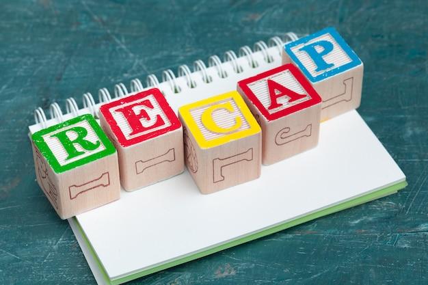 Bloco de notas na mesa de madeira e blocos de madeira alfabeto