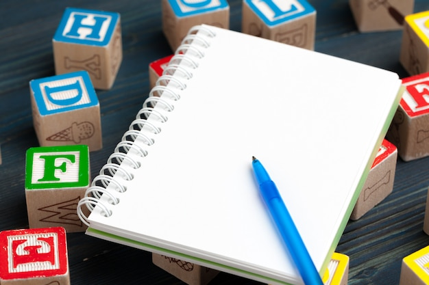 Bloco de notas na mesa de madeira e blocos de madeira com alfabeto
