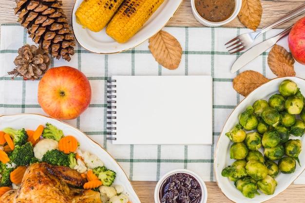 Bloco de notas na mesa festiva com comida
