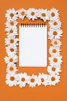 Bloco de notas no quadro de flores margarida