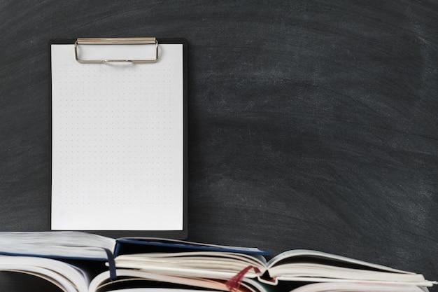 Bloco de notas no quadro-negro da escola com material de escritório