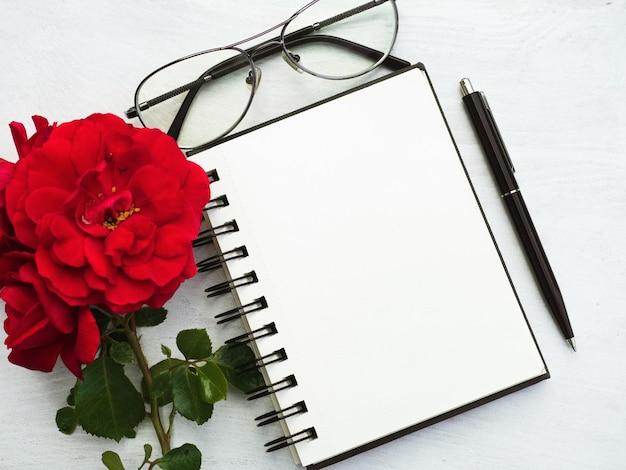 Bloco de notas, óculos, caneta e flor