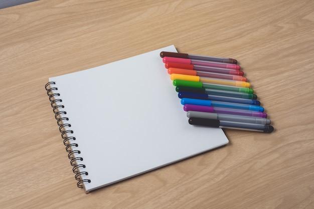Bloco de notas ou caderno com muitas canetas coloridas na mesa de madeira marrom
