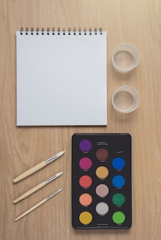Bloco de notas ou caderno com muitas canetas coloridas, pincel e paleta de aguarela na mesa de madeira marrom. usando para artes e educação