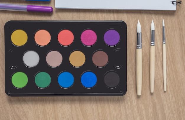 Bloco de notas ou caderno com muitas canetas coloridas, pincel e paleta de aquarela