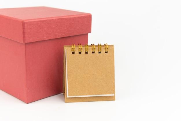 Bloco de notas ou calendário com caixa de presente em fundo branco. conceito de presente. copie o espaço.