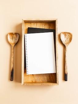 Bloco de notas ou livro de receitas de cozinha simulado para texto culinário em bandeja de madeira e colheres de pau