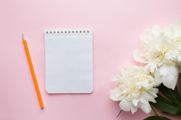 Bloco de notas para a peônia das flores brancas do texto no fundo do rosa pastel.