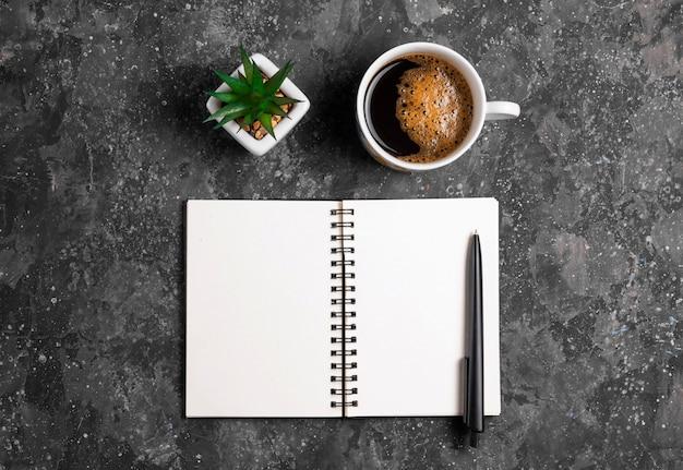 Bloco de notas para anotações com caneta, cacto e café na mesa cinza