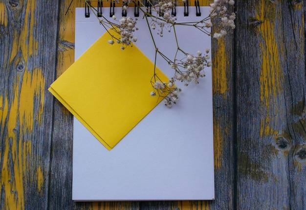 Bloco de notas para anotações e flores brancas em um fundo amarelo, vista superior