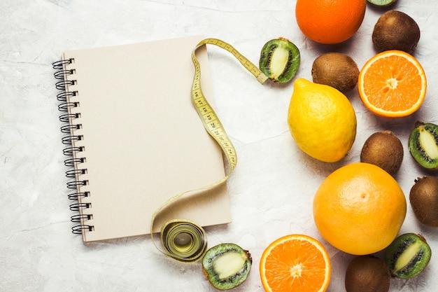 Bloco de notas para entradas, fita métrica e frutas orgânicas em um fundo de pedra clara