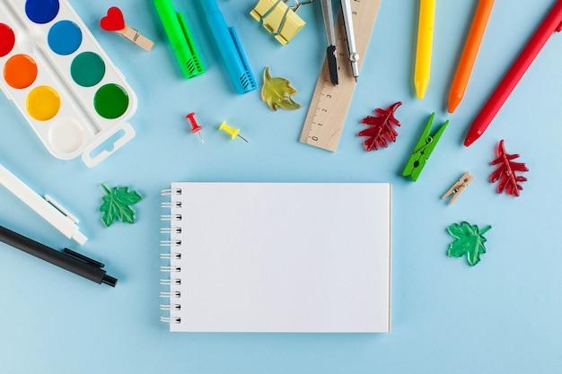 Bloco de notas para o seu texto rodeado por artigos de papelaria da escola em um fundo azul.