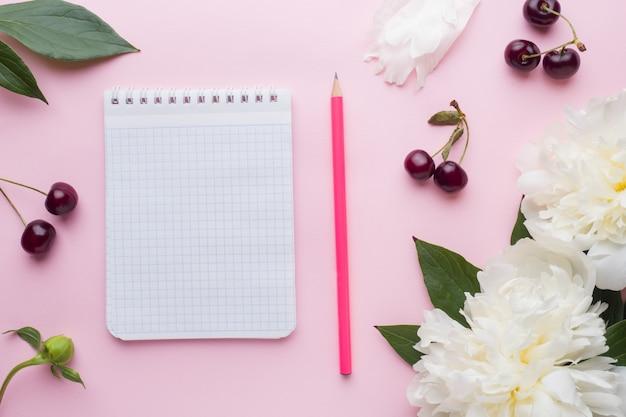 Bloco de notas para texto branco flores peônia cereja bagas na superfície rosa pastel