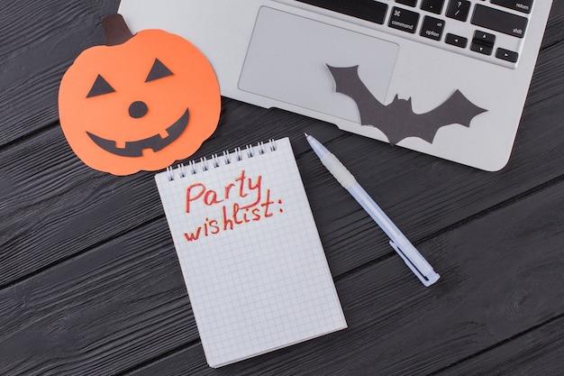 Bloco de notas para uma lista de desejos de uma festa de halloween. laptop com abóbora de papel e morcego. mesa de madeira preta no fundo.