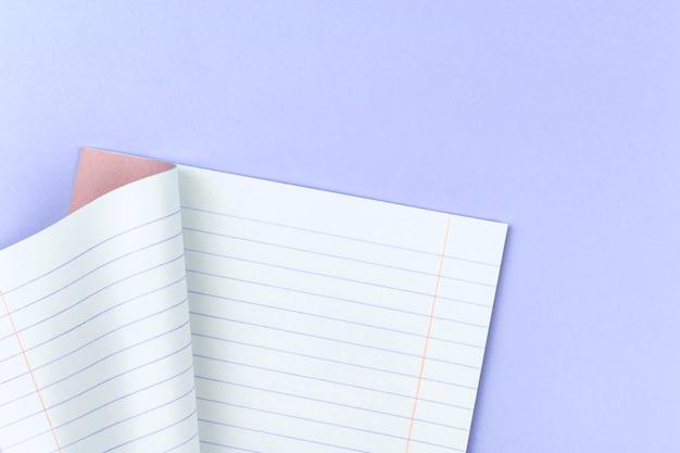 Bloco de notas pautado aberto para a escola em um fundo roxo pastel da área de trabalho da mesa do escritório, espaço de cópia e foto de vista superior