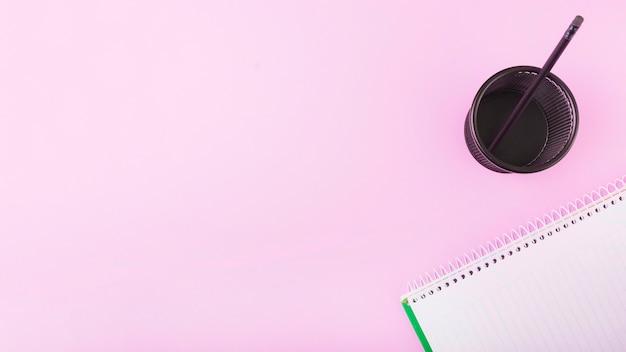 Bloco de notas perto de copo plástico com lápis no fundo rosa