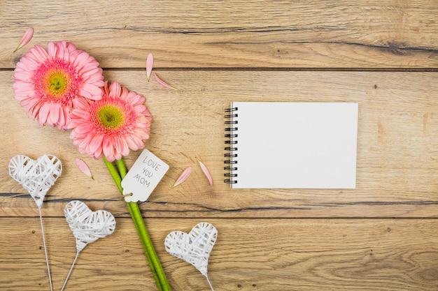 Bloco de notas perto de flores frescas com tag perto de corações ornamentais em varinhas