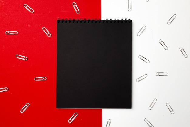 Bloco de notas preto cercado por clipes de papel, vista superior, espaço de cópia