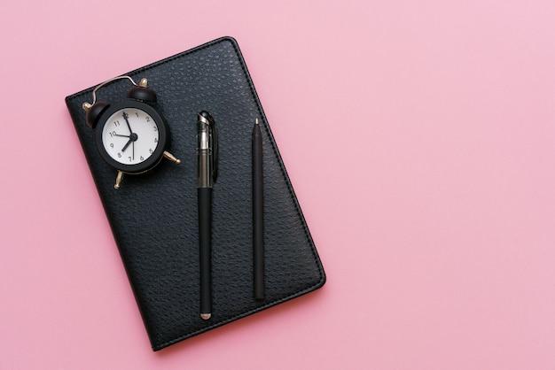 Bloco de notas preto com caneta e despertador em uma superfície rosa
