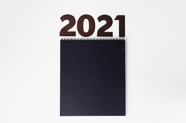 Bloco de notas preto com o número 2021 na vista superior da superfície branca, espaço para cópia
