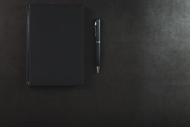 Bloco de notas preto com uma caneta preta em um fundo preto.