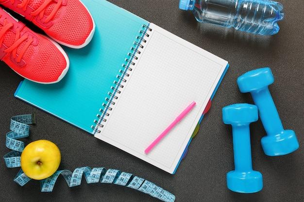 Bloco de notas, uma garrafa de água, uma maçã, uma corda de pular, halteres. dieta saudável, estilo de vida, conceito de halteres, exercício