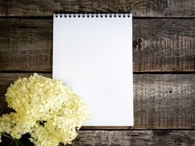 Bloco de notas vazio aberto branco e um buquê de flores