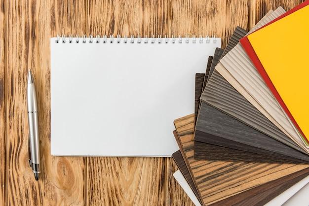 Bloco de notas vazio com catálogo de piso de madeira para novo design de sua casa