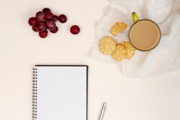 Bloco de notas vazio com cookies e uvas