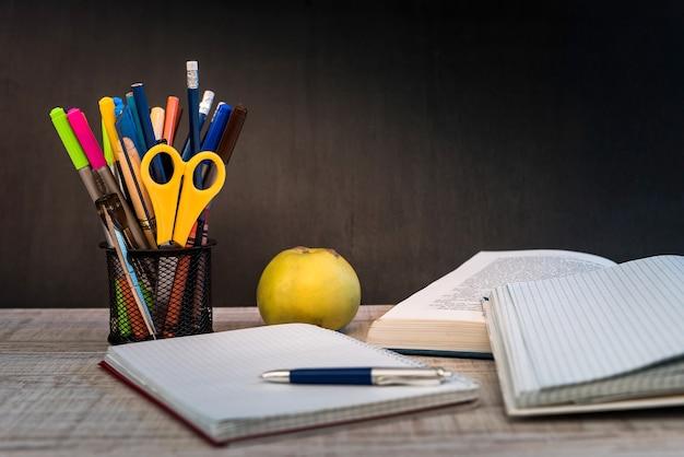 Bloco de notas vazio na mesa do professor contra o conceito de educação do quadro-negro