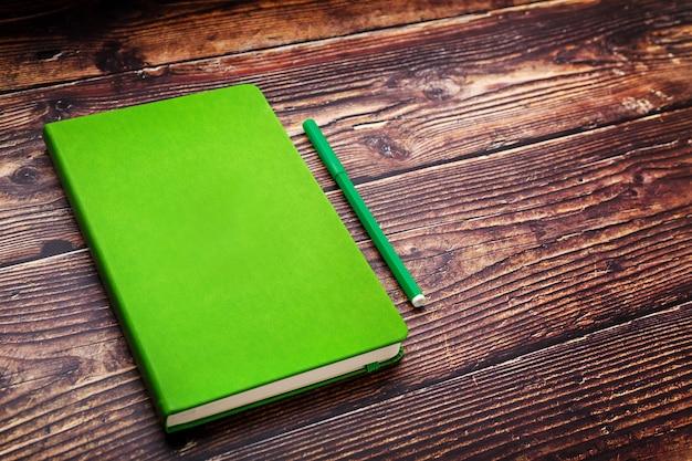 Bloco de notas verde com uma caneta com ponta de feltro em uma mesa de madeira marrom, vista superior.