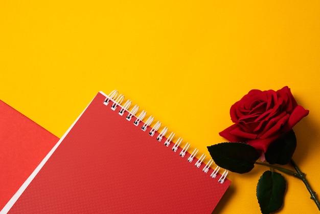 Bloco de notas vermelho e rosa em uma mesa amarela com copyspace