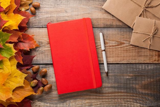 Bloco de notas vermelho na mesa de madeira velha.