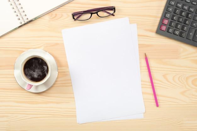 Bloco de notas, xícara de café, planta em vaso verde, material de escritório na mesa de madeira. postura plana