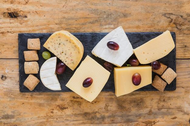 Bloco de queijo com uvas e pastelaria na placa de pedra ardósia sobre a mesa de madeira