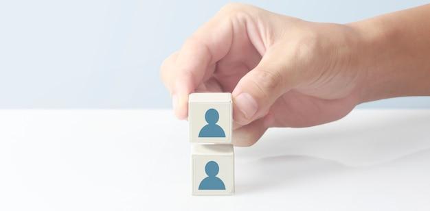 Bloco do cubo na mão com o ícone do usuário. conceito de hierarquia de negócios