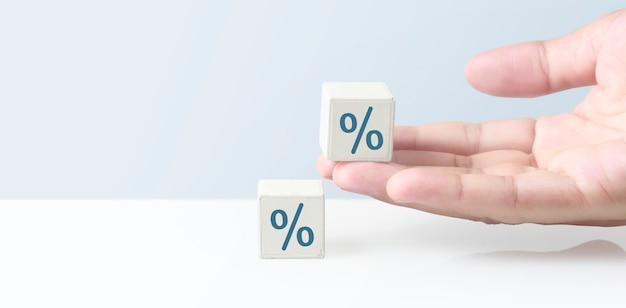 Bloco do cubo na mão com sinal de porcentagem