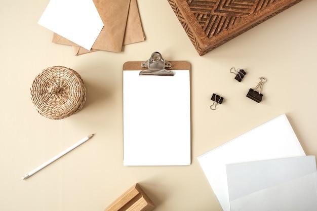 Bloco do tablet da área de transferência com a folha de papel em branco na mesa bege. camada plana, vista superior