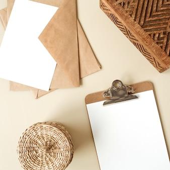 Bloco do tablet da área de transferência com a folha de papel em branco na mesa bege. postura plana